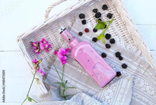Foto op Canvas Milkshake смузи из ежевики в бутылке со свежей ягодой и цветами