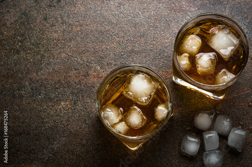 Whiskey with ice in glass. Top view on dark stone table.