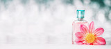 Perfume bottle with pink flower at bokeh background, front view, banner. Beauty and perfumery concept - 168477223
