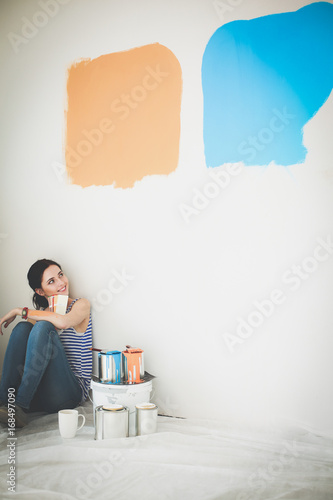Woman choosing paint colour from swatch for new home sitting on wooden floor. Woman in the house