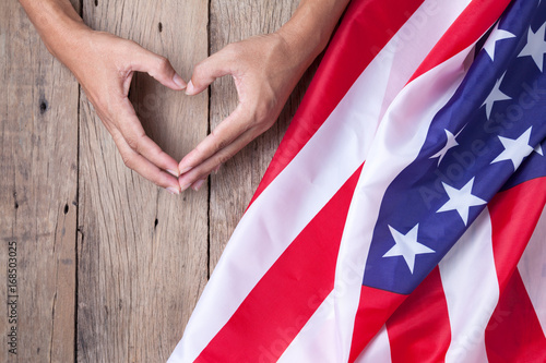 Gesture made by hands showing symbol of heart with american flag on old wooden background Poster