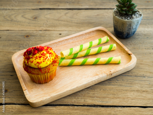 Sticker Yellow cupcakes put on wooden plates along with green striped wafer. Beside of cupcake have cactus on the wood table