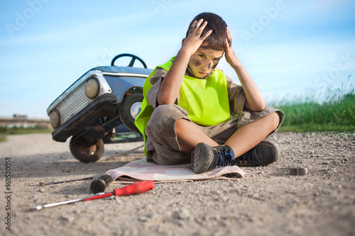 help on the road, a young boy with his toy car