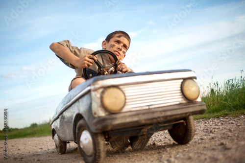 Young boy driving a vintage toy car, beautiful sunny day