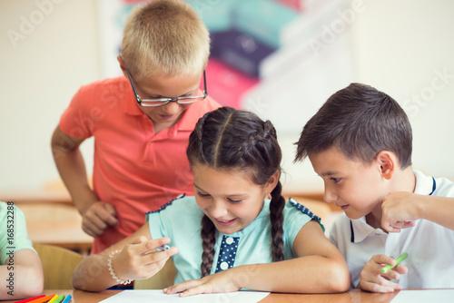 Group of school children learning at klassroom in school