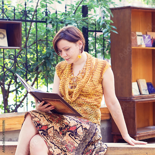 Young woman reading the book in the park