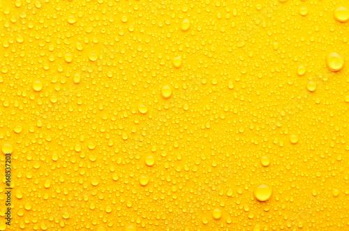 Leinwandbild Motiv water drops on a yellow background