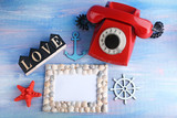 Red retro telephone with photo frame and seashells on blue wooden table