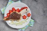 Funny dinosaur shaped pancake with strawberry, banana and chocolate