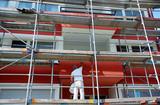 Maler auf Gerüst streicht die Außenfassade eines Mehrfamilienhauses - 168539656