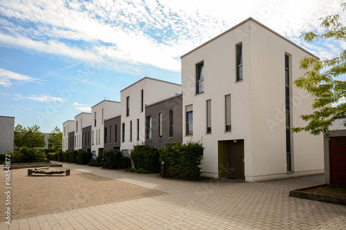 Leinwanddruck Bild Modern townhouses in a residential area, new apartment buildings with green outdoor facilities in the city