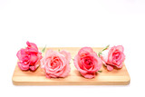 Pink roses lie on wooden board isolated