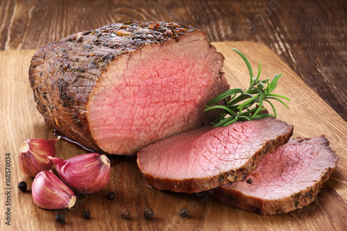 Sticker Baked meat, garlic and rosemary on a wooden background. Roast beef.