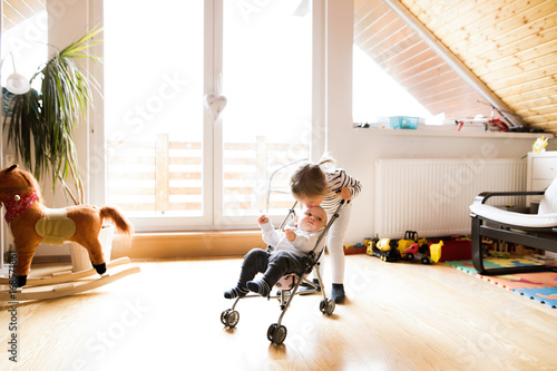 Little girl at home with baby brother in toy stroller.