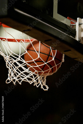 Basketball going through the basket at a sports arena Poster