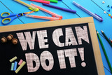 The text We can do it on a black chalkboard on the table with school accessories (pens, pencils, brushes)