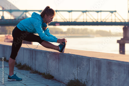 Young woman jogger  running  by the river in the morning Poster