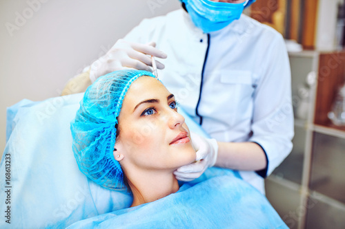 Fototapeta Woman with marked face receiving botox injection