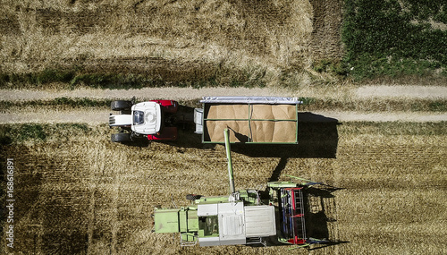 Aluminium Trekker Tractor with trailer and harvester and grain from above in summer