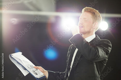 Handsome red-haired speaker rehearsing speech for effective business presentatio Poster