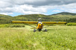 Small aircraft taking off on scenic country meadow