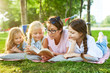 Teacher and three little girls reading stories from book while relaxing on grass