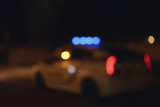 Blurred view of police car on road at night