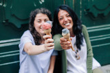 Two women friends eating ice-cream together in city during summer - 168643297