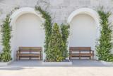 две скамейки в парке у стены в зелени