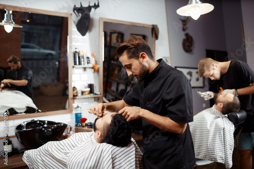 Barber working with client in chair Poster
