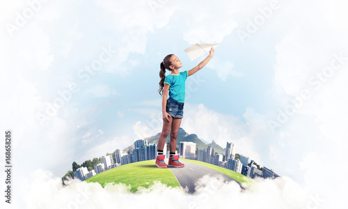 Concept of careless happy childhood with girl dreaming about fut