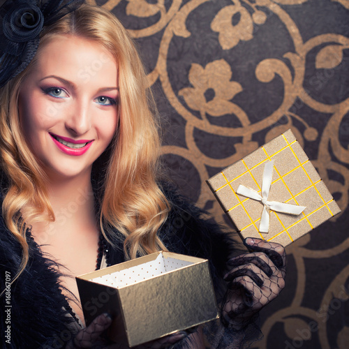 Plakát beautiful retro woman holding a golden gift box