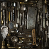 Cutlery, forks, spoons, and knives on dark wooden background