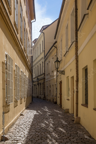 Papiers peints Ruelle etroite Narrow and empty cobblestone street and old buildings at the Old Town in Prague, Czech Republic on a sunny day.