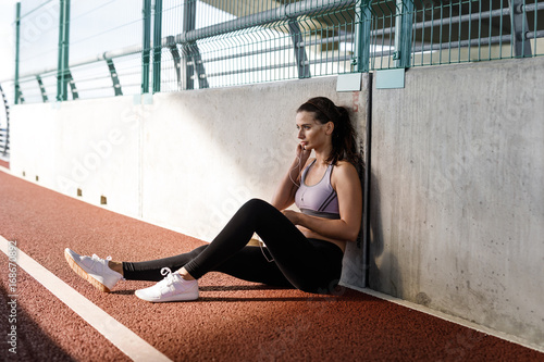 Poster Young sportswoman with earphones sitting at wall, taking a break