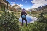 Fototapety a young woman hiking next to a mountain lake