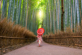 Woman in traditional Yukata with red umbrella at bamboo forest of Arashiyama © f11photo