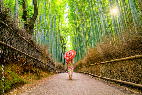 Papiers peints Bambou Woman in traditional Yukata with red umbrella at bamboo forest of Arashiyama