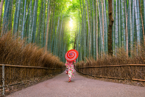 Fotobehang Kyoto Woman in traditional Yukata with red umbrella at bamboo forest of Arashiyama