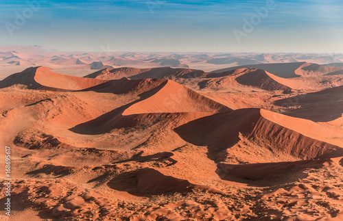 Foto op Canvas Koraal Namib desert, Sossusvlei. Aerial panorama of the big red dunes in Sossusvlei area taken from the helicopter. Annual growth of the area of sand. Global warming on the planet.