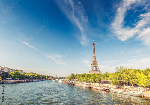 Sticker The Eiffel Tower in Paris, France, on a sunny day with the river Seine and dramatic clouds.  Colourful travel background. Popular travel destination