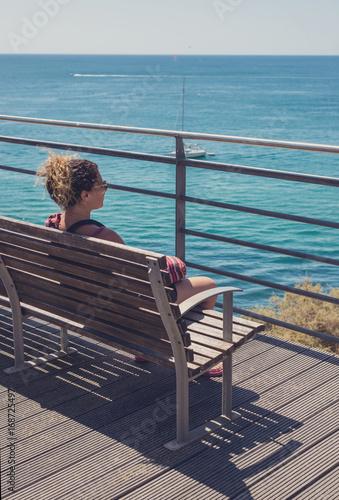 femme sur un banc contemplant la la mer Poster