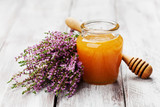 Delicious fresh honey in pot or jar and flowers heather on wooden vintage background.