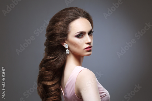 Beauty portrait of a girl with an elegant bridal woven voluminous hair on long dark hair. © ksi