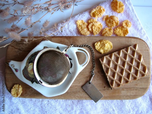 Sticker Chocolate wafer, corn flakes and tea strainer on a wooden planks and a towel