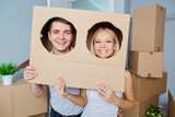 Funny couple with a box on the head in a new house. The concept of housewarming. - 168746877