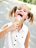Cute smiling little girl eating an ice cream - 168747059