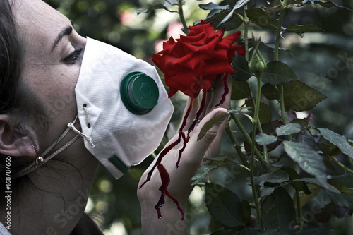 Poster A girl in a mask sniffs a rose, supporting her with a palm over which the blood sticks