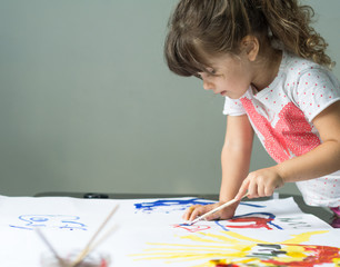 Four years old child is drawing at home. Beautiful little girl with paint brush and watercolor.