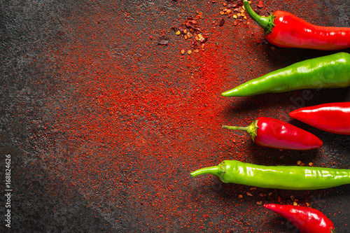 Papiers peints Hot chili Peppers Red and green hot pepper and dry ground pepper on a dark background